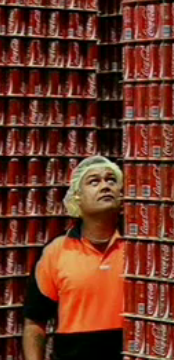 A screengrab of a Coca-Cola employee looking up a pallet of Coke Classic cans.